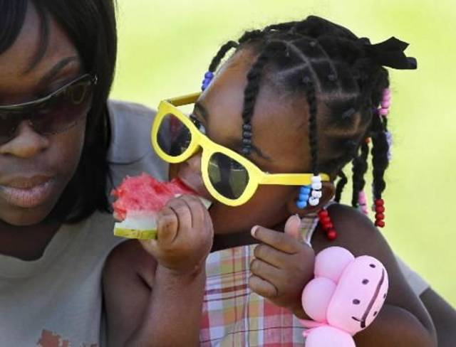 Bre'Onna Davis, of Oklahoma City, eats a slice of watermelon during the 2012 Septemberfest. Photo by Jim Beckel, The Oklahoman Archive