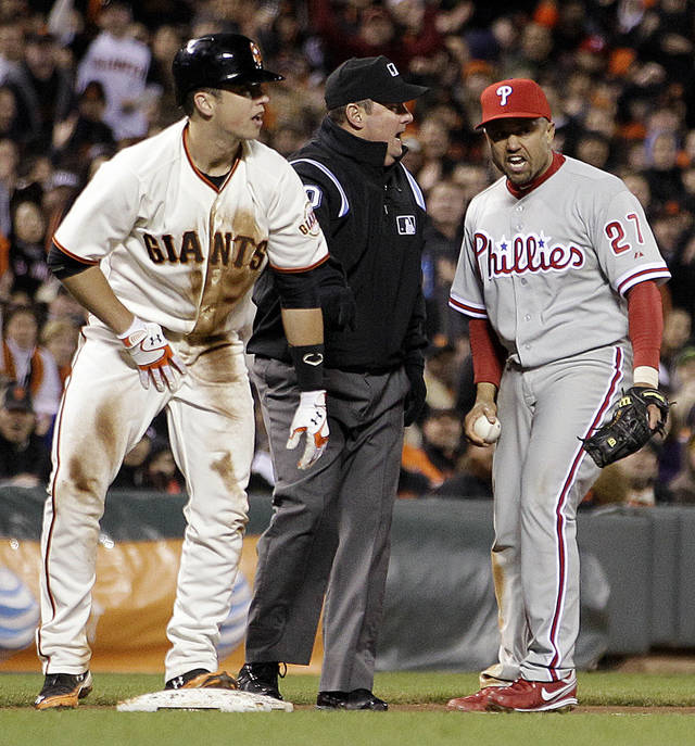 Philadelphia Phillies third baseman Placido Polanco, right, argues a call with umpire Marty Foster, center, as San Francisco Giants' Buster Posey, left, stands safe at third base during the fifth inning of a baseball game Tuesday, April 17, 2012, in San Francisco. Posey was ruled safe with a steal of third base. (AP Photo/Ben Margot)
