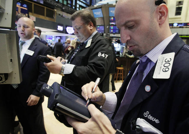 In this Dec. 20, 2011 photo, Steven Marcus, right, works with fellow traders on the floor of the New York Stock Exchange. European stock markets extended gains Wednesday, Dec. 21, on a wave of pre-holiday optimism after the European Central Bank loaned a record amount to the continent's banks in an effort to bolster Europe's stressed financial system. (AP Photo/Richard Drew)