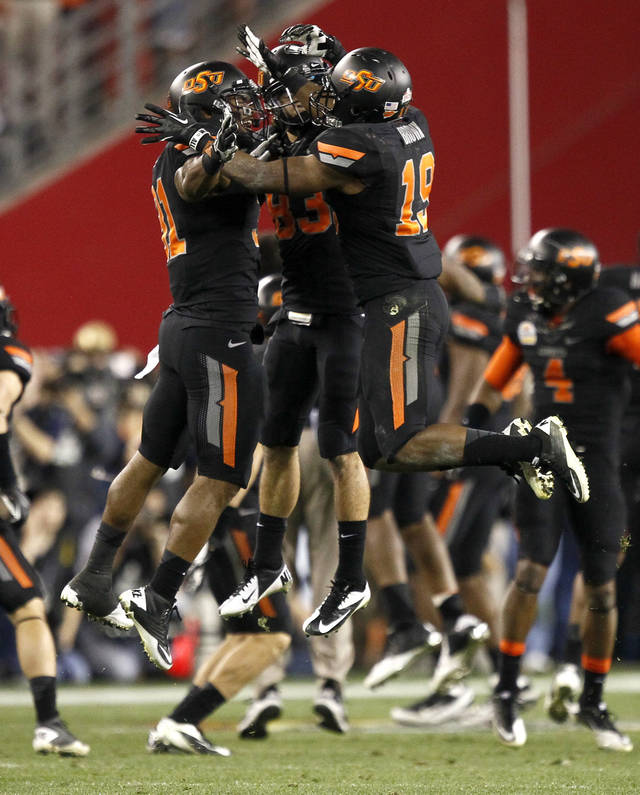 Oklahoma State cornerback Brodrick Brown (19), Colton Chelf, center, and Shaun Lewis, right, celebrate a missed field goal attempt by Stanford during overtime of the Fiesta Bowl NCAA college football game Monday, Jan. 2, 2012, in Glendale, Ariz. Oklahoma State won 41-38 in overtime. (AP Photo/Matt York)  ORG XMIT: PNP148