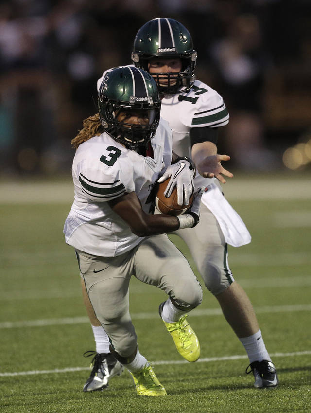 Peyton Gavras (13) hands the ball off to Bryan Payne (3) during a high school football game between Midwest City and Norman North in Midwest City, Friday, Sept. 21, 2012.  Photo by Garett Fisbeck, The Oklahoman