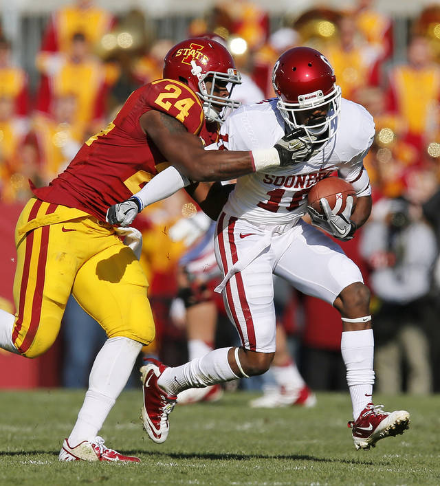 Iowa State's Durrell Givens (24) tackles Oklahoma's Jalen Saunders (18) after a catch during a college football game between the University of Oklahoma (OU) and Iowa State University (ISU) at Jack Trice Stadium in Ames, Iowa, Saturday, Nov. 3, 2012. Photo by Nate Billings, The Oklahoman