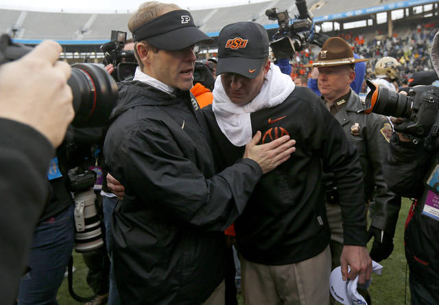 Oklahoma State coach Mike Gundy meets with Purdue interim coach Patrick Higgins after the Heart of Dallas Bowl football game between Oklahoma State University and Purdue University at the Cotton Bowl in Dallas, Tuesday, Jan. 1, 2013. Oklahoma State won 58-14. Photo by Bryan Terry, The Oklahoman