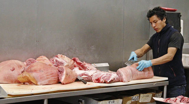 Butcher Freddie Quina cuts meat Wednesday at Super Cao Nguyen in Oklahoma City. AP Photo