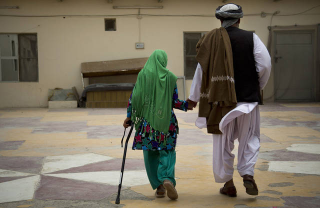Zardana, 11, holds the hand of her father, Samiullah, after an interview in Kandahar, Afghanistan on Monday, April 22, 2013. Surviving family members recalled how a U.S. soldier attacked their home on March 11, 2012, shooting Zardana in the head. She spent about two months recovering at the Kandahar Air Base hospital and three more at a naval hospital in San Diego receiving rehabilitation therapy, accompanied by her father, Samiullah. (AP Photo/Anja Niedringhaus)