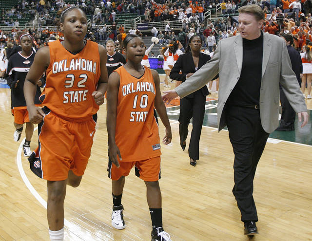 Oklahoma State Universitiy head coach Kurt Budke walks off the court with Shaunte Smith (32) and Andrea Riley (10) after the loss to Bowling Green in the first round game of the women's NCAA Tournament in the Jack Breslin Arena at Michigan State University on Sunday, March 18, 2007, in East Lansing, Mich.   staff photo by CHRIS LANDSBERGER