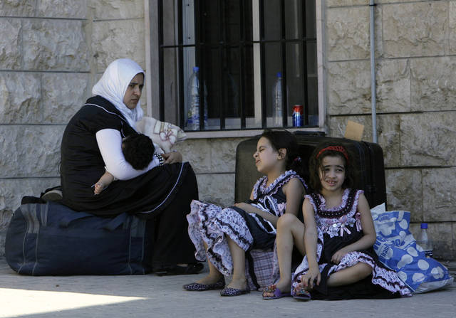 A Syrian woman sits with her children outside the Lebanese immigration office at the Masnaa border post shortly after crossing from Syria to Majdal Anjar, Lebanon Monday, July 23, 2012. After a bloody, weeklong siege in the Syrian capital, Damascus, residents who stayed behind are facing hours-long queues for petrol and bread, stinking piles of rubbish in the streets and scenes of unimaginable destruction while thousands of Syrians have escaped to Lebanon over the past week. (AP Photo/Bilal Hussein)