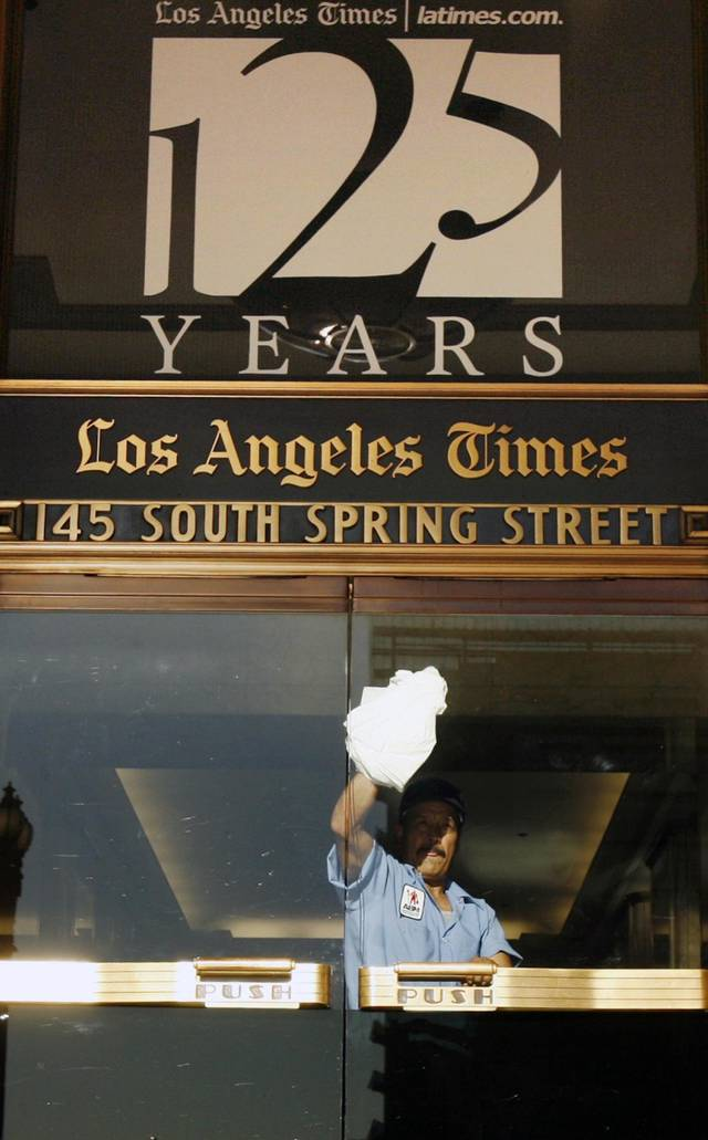"FILE - In this Nov. 16, 2006 file photo, a worker cleans an entrance to the Los Angeles Times building in Los Angeles.   Federal authorities allege that Matthew Keys provided hackers with login information to access the Tribune Company's computer system in December 2010. Keys had been fired months before from a Sacramento television station owned by Tribune. Keys was a web producer for KTXL. Tribune also owns the Times. The investigators allege that Keys gave a hacker named ""Sharpie"" the information in an Internet chat room frequented by hackers and urged the hacker to do some damage to the Tribune company. (AP Photo/Ric Francis)"