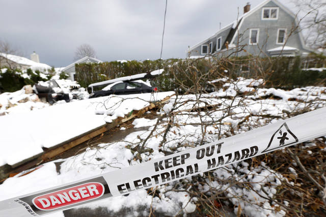 A down utility poll rests on top of a vehicle as snow covered debris from Superstorm Sandy lay in the middle of a street following a nor'easter storm, Thursday, Nov. 8, 2012, in Point Pleasant, N.J. The New York-New Jersey region woke up to wet snow and more power outages Thursday after the nor'easter pushed back efforts to recover from Superstorm Sandy, that left millions powerless and dozens dead last week. (AP Photo/Julio Cortez)