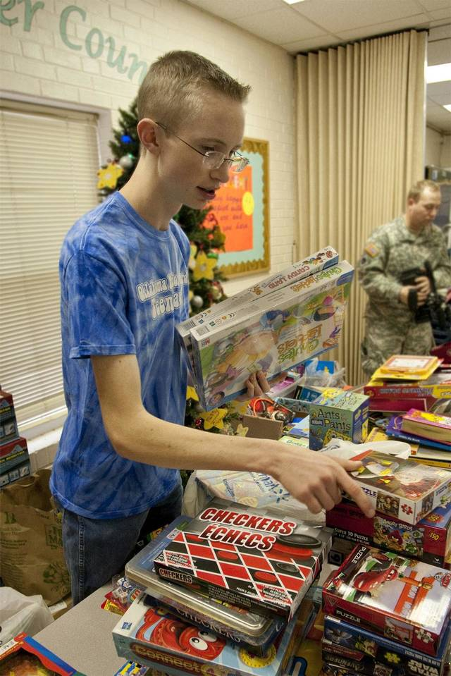 Christian Keenan, 15, of Piedmont, sorts donated toys at the Positive Tomorrows School in Oklahoma City. Keenan is a member of the Oklahoma National Guard Teen Panel.  Photo provided by Maj. Geoff Legler,  Oklahoma National Guard Office of Public Affairs
