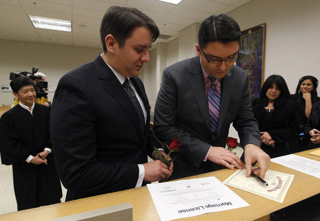 Judge Mary Yu, left, looks on as Brendon Taga, right and Jesse Page, of Vashon Island, Wash., sign their wedding certificate after taking their wedding vows in the early morning hours, becoming among the first gay couples to legally wed, Sunday, Dec. 9, 2012, in Seattle. Gov. Chris Gregoire signed a voter-approved law legalizing gay marriage Wednesday, Dec. 5 and weddings for gay and lesbian couples began in Washington on Sunday, following the three-day waiting period after marriage licenses were issued earlier in the week. (AP Photo/Elaine Thompson)