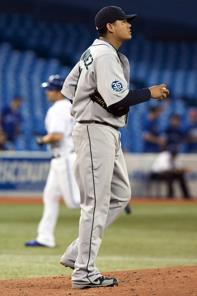 Seattle Mariners starting pitcher Felix Hernandez stands on the mound as Toronto Blue Jays' Adam Lind rounds the bases on his two-run home run during the first inning of a baseball game, Thursday, Sept. 13, 2012, in Toronto. (AP Photo/The Canadian Press, Frank Gunn)