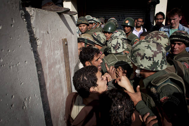 Egyptian protesters scuffle with army soldiers near the presidential palace in Cairo, Egypt, Sunday, Dec. 9, 2012. Egypt's liberal opposition has called for more protests on Sunday after the president made concessions overnight that fell short of their demands to rescind a draft constitution going to a referendum on Dec. 15. (AP Photo/Nasser Nasser)