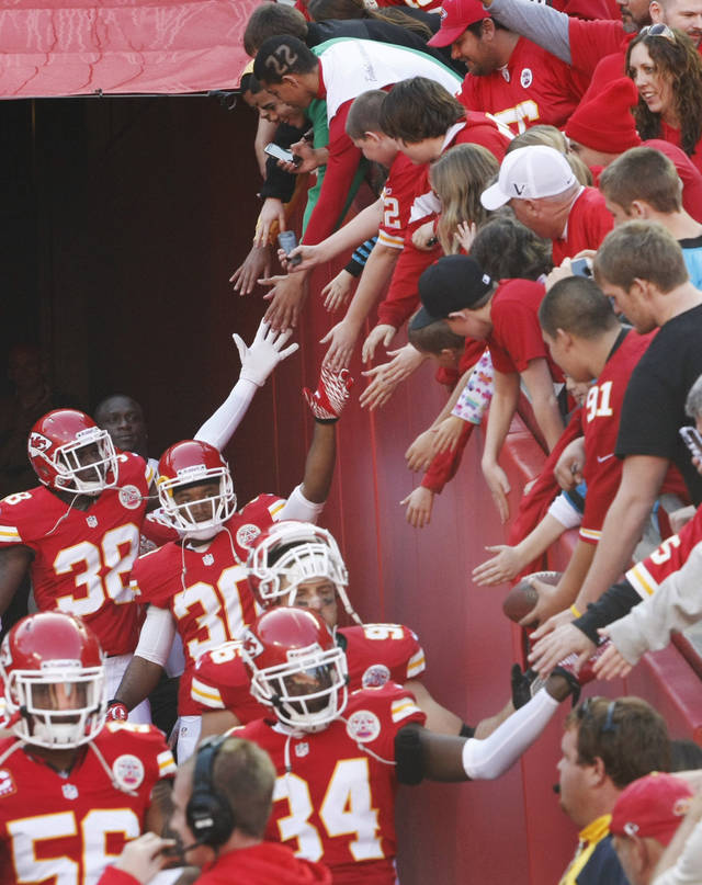 ADDS LAST SENTENCE - Kansas City Chiefs players greet fans as they exit the tunnel before an NFL football game against the Carolina Panthers at Arrowhead Stadium in Kansas City, Mo., Sunday, Dec. 2, 2012. The game came one day after Chiefs' Jovan Belcher fatally shot his girlfriend and turned a gun on himself as GM Scott Pioli and coach Romeo Crennel looked on. (AP Photo/Colin E. Braley)