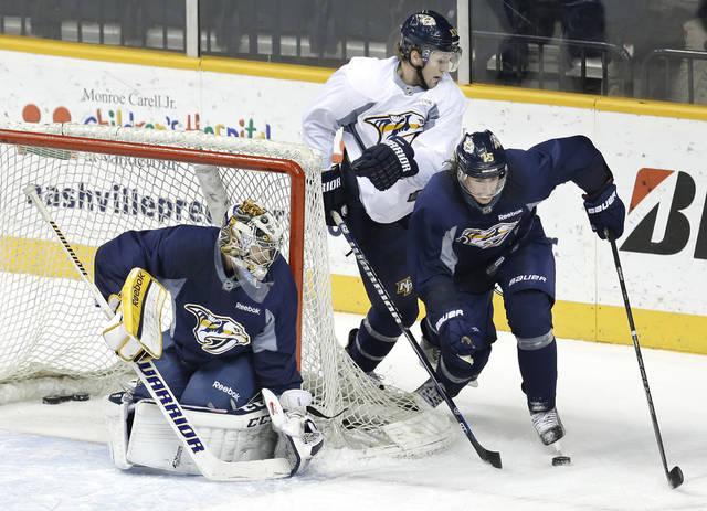 Nashville Predators goalie Pekka Rinne, left, of Finland, watches as Nick Spaling, center, and Craig Smith, right, battle for the  puck at NHL hockey training camp on Wednesday, Jan. 16, 2013, in Nashville, Tenn. The shortened, 48-game season begins Saturday, Jan. 19. (AP Photo/Mark Humphrey)