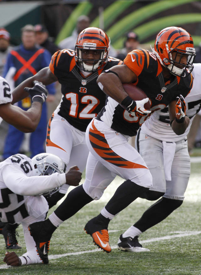 Cincinnati Bengals running back Cedric Peerman (30) runs past Oakland Raiders middle linebacker Rolando McClain (55) in the first half of an NFL football game, Sunday, Nov. 25, 2012, in Cincinnati. (AP Photo/Tom Uhlman)