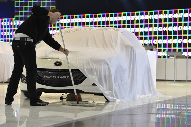 A worker cleans the floor next to a car at the Mazda booth during last preparations prior to the opening of the press preview days at the 83nd Geneva International Motor Show in Geneva, Switzerland, Saturday, March 2, 2013. The Motor Show will open its gates to the public from March 7 to 17, presenting more than 260 exhibitors and more than 130 world and European premieres. (AP Photo/Keystone, Martial Trezzini)