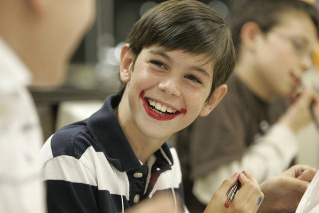 Camp Funnybone camper Sam Davis, center, laughs with camper Chris Shelley, left, while applying clown makeup during a class at Heritage Hall on Tuesday, June 24, 2008. By Amy Rymer, The Oklahoman