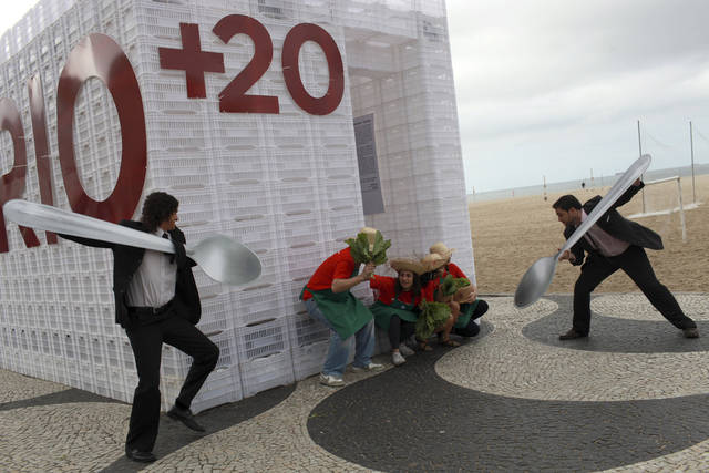"""COMMERCIAL PHOTO - Protesters calling for a significant and urgent change in the global food system 'force feed"""" two giant spoons to illustrate the current industrial scale agriculture production on Copacabana Beach on the fringes of the United Nations Rio+20 Sustainable Development Conference in Rio de Janeiro on Thursday, June 21, 2012. ActionAid are calling for World leaders attending the Rio+20 Summit to initiate a much needed shift in the global food system, from large-scale industrial agriculture, to a model that places the lives and livelihoods of small-scale farmers at its heart. (Dado Gladieri for ActionAid via AP Images)"""