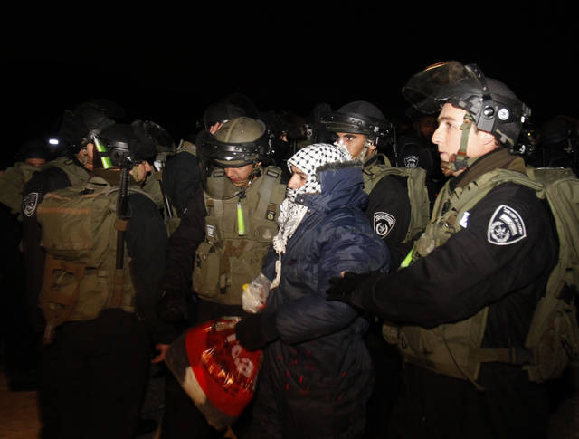 "Israeli border police evict a Palestinian activist from an area known as E-1 near Jerusalem, Sunday, Jan 13, 2013. Palestinian activists erected tents in the area on Friday saying they wanted to ""establish facts on the ground"" to stop Israeli construction in the West Bank. The Palestinian activists were borrowing a phrase and a tactic, usually associated with Jewish settlers, who believe establishing communities means the territory will remain theirs once structures are built. (AP Photo/Nasser Shiyoukhi)"