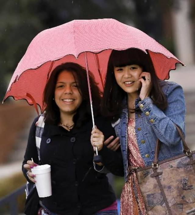 Vanessa Klie, left, and Yueru Jin, students at Oklahoma Christian University, share an umbrella as light right falls while the pair walks across campus to a parking lot Thursday around noon, Sept. 27, 2012. Photo by Jim Beckel
