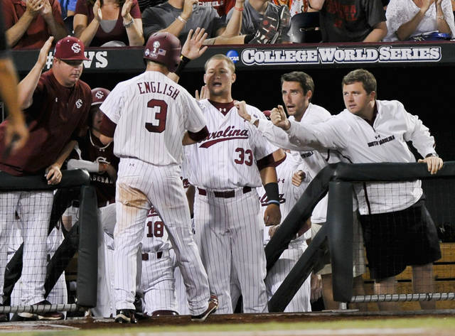 South Carolina's Tanner English (3) is greeted at the dugout by Kyle Martin (33) and others after he scored against Arkansas on a single by Joey Pankake, in the fifth inning of an NCAA College World Series baseball elimination game in Omaha, Neb., Friday, June 22, 2012. The winner advances to play Arizona in the championship series. (AP Photo/Ted Kirk)