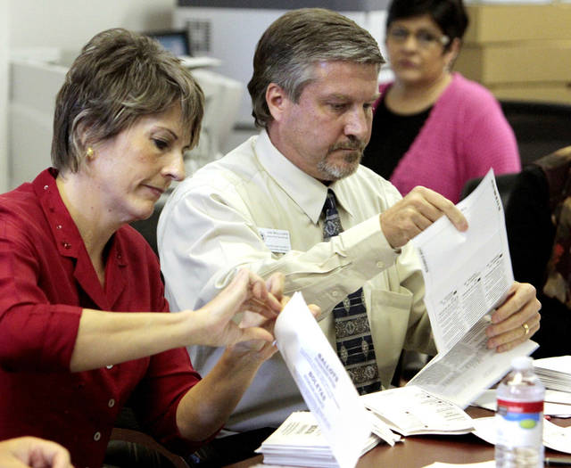 Cleveland County Election Board Chairman Lisa Shrieves and board Executive Secretary Jim Williams open misplaced absentee ballots Friday.  PHOTO BY STEVE SISNEY, THE OKLAHOMAN