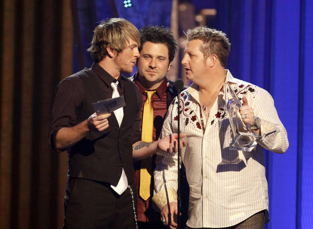 From right, Gary LeVox, Jay DeMarcus and Joe Don Rooney of the band Rascal Flatts accept the Vocal Group of the Year award during the 42nd Annual CMA Awards show on Wednesday Nov. 12, 2008 in Nashville, Tenn.  (AP Photo/Darron Cummings) ORG XMIT: TNLS161