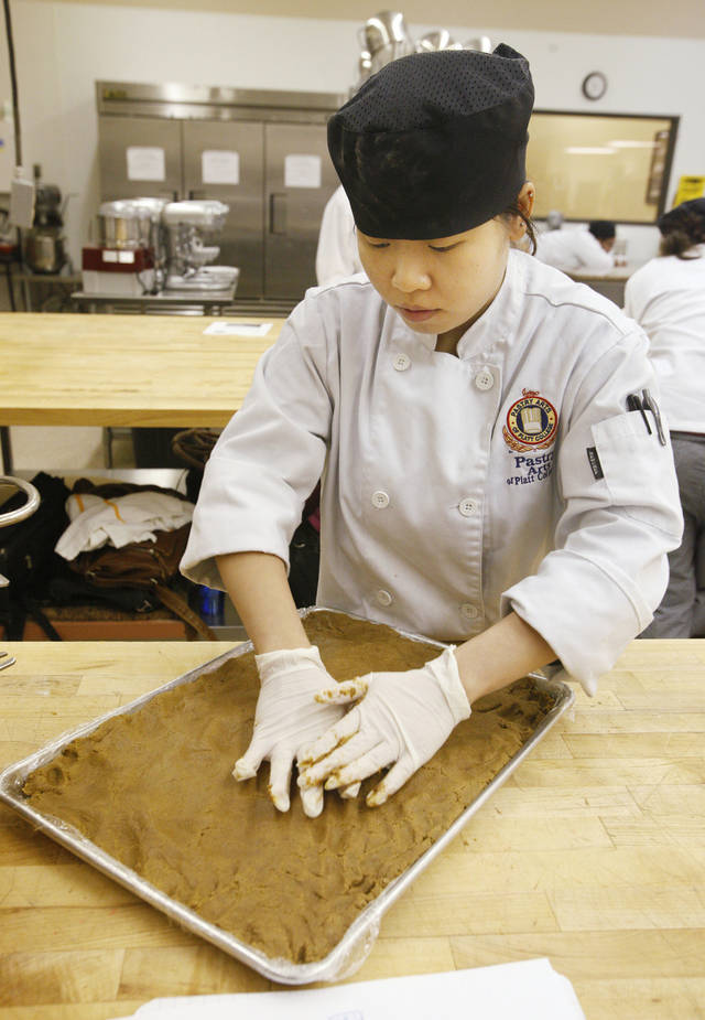 Platt College pastry arts student Hoi So, of Oklahoma City, presses dough into a pan to bake for gingerbread houses. Students at the school in Moore will submit decorated houses for a contest on Friday.  PHOTO BY PAUL B. SOUTHERLAND, THE OKLAHOMAN