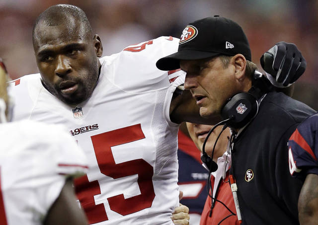File - In this Aug. 18, 2012, file photo, San Francisco 49ers' Brandon Jacobs (45) is helped off by head coach Jim Harbaugh in the first quarter of an NFL preseason football game against the Houston Texans in Houston. Jacobs has posted advice on Twitter with a reference to never working �in a place where you hate your boss so much.�  The hash tag: �YouLiveAndYouLearn.� Jacobs had terrible timing with the tweet Thursday, Nov. 15, 2012, considering coach Harbaugh was hospitalized for what the team called a �minor procedure� for an irregular heartbeat. In the locker room soon after his post, Jacobs said people shouldn�t �assume� his remarks were football-related, then followed up with more tweets. He made one post saying that �football is not my life.� (AP Photo/David J. Phillip, File)