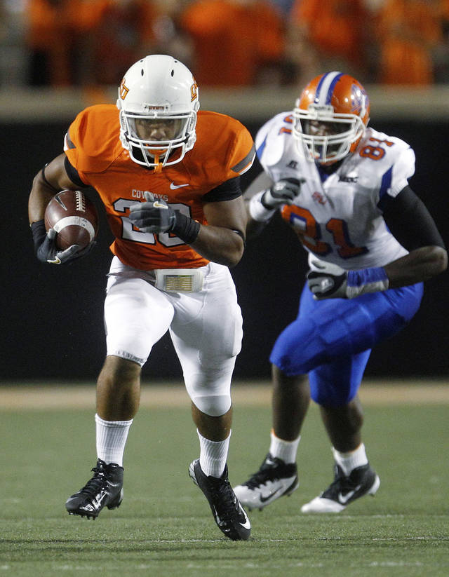 In this Saturday, Sept. 1, 2012, photo, Oklahoma State running back Corey Bennett (20) carries in front of Savannah State defensive lineman Jovanta Mobley (81) in an NCAA college football game in Stillwater, Okla. Bennett was the fifth running back to get in against Savannah State and ended up with a team-high 12 carries for 91 yards and a touchdown. (AP Photo/Sue Ogrocki)