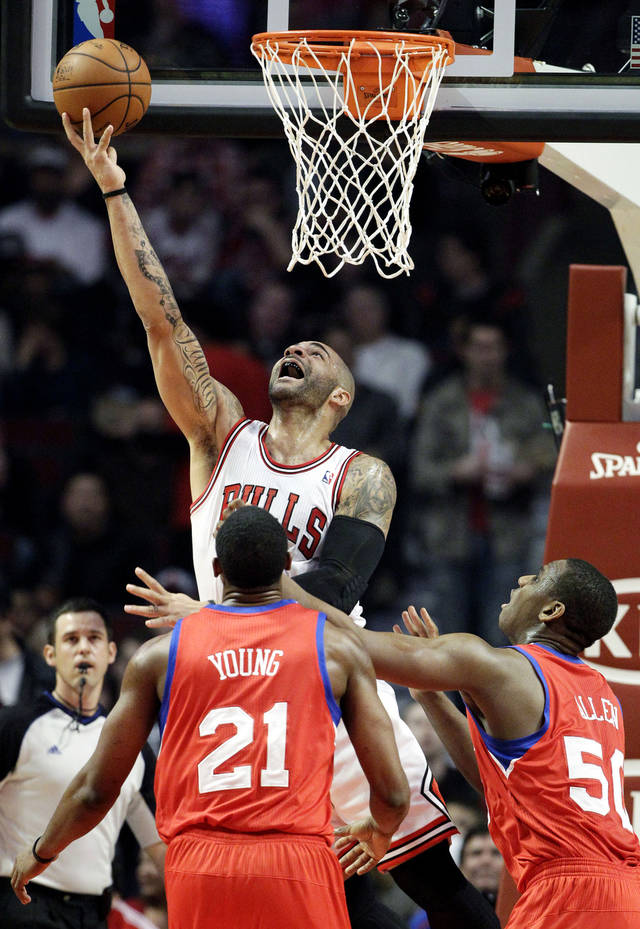 Chicago Bulls forward Carlos Boozer, top, shoots as Philadelphia 76ers forward Thaddeus Young (21) and center Lavoy Allen (50) look on during the first half of an NBA basketball game in Chicago on Saturday, Dec. 1, 2012. (AP Photo/Nam Y. Huh)
