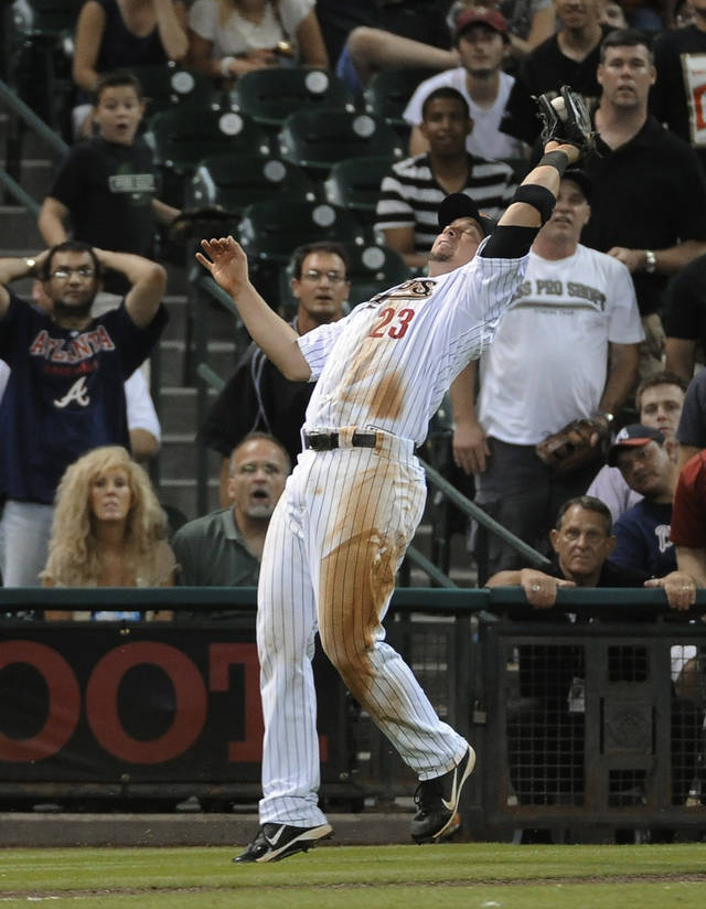 Houston Astros' Chris Johnson makes a catch along the warning track for the out on Atlanta Braves' Freddie Freeman in the eighth inning of a baseball game Monday, April 9, 2012, in Houston. The Astros won 8-3. (AP Photo/Pat Sullivan)