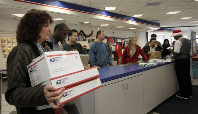 FILE - This Dec. 19, 2011 file photo shows people in line at the U.S. Postal Service Airport station in Los Angeles. Emboldened by rapid growth in e-commerce shipping, the cash-strapped U.S. Postal Service is moving aggressively this holiday season to start a premium service for the Internet shopper seeking the instant gratification of a store purchase: same-day package delivery. (AP Photo/Nick Ut, File)