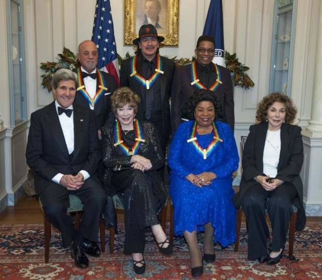 Secretary of State John Kerry, with the 2013 Kennedy Center honorees, from left, seated Shirley MacLain, and Martina Arroyo, along with Teresa Heinz Kerry. Standing are Billy Joel, Carlos Santana, and Herbie Hancock, pose for a photo at the State Department for the Kennedy Center Honors gala dinner on Saturday, Dec. 7, 2013 in Washington. (AP)