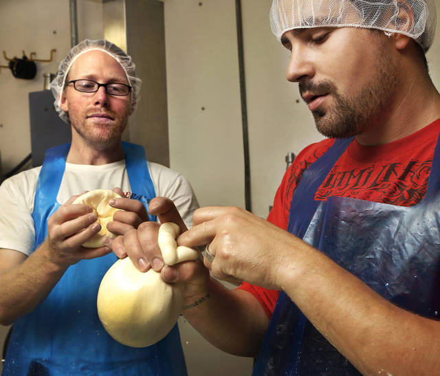 Shawn Duffly, left, and Kyle Arpoika mold caciocavallo-style cheese at Lovera's Italian Market in Krebs. <strong>Jim Beckel - THE OKLAHOMAN</strong>