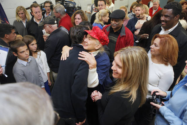 Matt Romney gets a hug from Charlotte Ambrose of Comstock Park on Monday, Nov. 5, at the Kent County Republican Headquarters. Grand Rapids was the first of several Michigan stops for Matt and his brother Josh. (AP Photo/The Grand Rapids Press, Emily Zoldaz ) ALL LOCAL TV OUT; LOCAL TV INTERNET OUT
