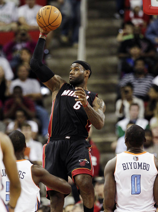 Miami Heat's LeBron James (6) saves the ball from going out of bounds as Charlotte Bobcat's DaJuan Summers and Bismack Biyombo (0) watch during the first half of an NBA preseason basketball game in Raleigh, N.C., Tuesday, Oct. 23, 2012. (AP Photo/Gerry Broome)