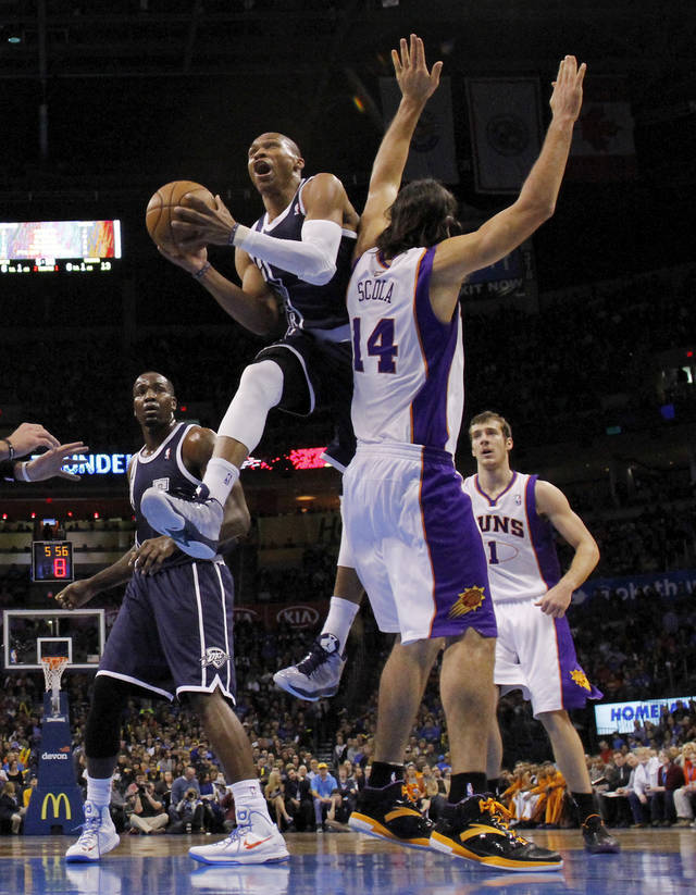 Oklahoma City Thunder's Russell Westbrook (0) drives around Phoenix Suns' Luis Scola (14) as the Oklahoma City Thunder play the Phoenix Suns in NBA basketball at the Chesapeake Energy Arena in Oklahoma City, on Monday, Dec. 31, 2012.  Photo by Steve Sisney, The Oklahoman