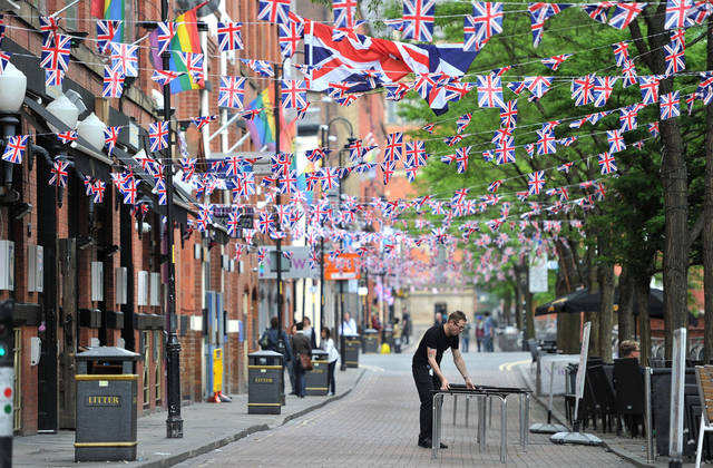 Preparations are made for a Jubilee street party on Canal Street in Manchester, England Friday June 1 2012. The patriotic bunting is ready, the golden carriage on standby, the boats freshly painted, the shops filled with royals souvenirs. The normal ebb and flow of British life gives way in the next four days to a series of street parties, flotillas, outdoor concerts and finally the appearance of an elderly great-grandmother on her balcony to wave to her subjects. The pageantry is very grand and very British.(AP Photo/Martin Rickett/PA Wire)
