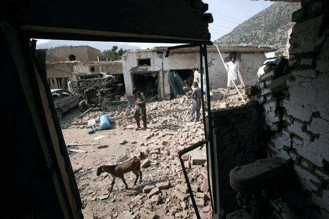 Pakistanis check the damage caused by a car bomb explosion, in the Pakistani town of Darra Adam Khel in the troubled Khyber Pakhtunkhwa province bordering Afghanistan, Saturday, Oct. 13, 2012. A powerful car bomb went off outside the offices of pro-government tribal elders in northwestern Pakistan on Saturday, killing several people, police said. (AP Photo/Mohammad Sajjad)