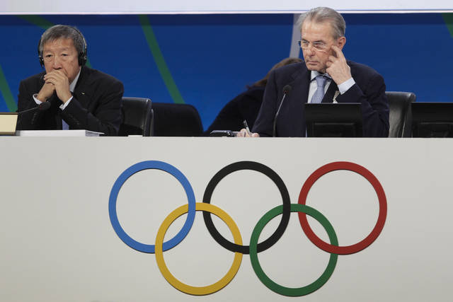 Jacques Rogge, president of the International Olympic Committee (IOC), right, and Singapore's Ser Miang Ng, IOC executive board member, left, listen to the wrestling presentation during the 125th IOC session in Buenos Aires, Argentina,  Sunday, Sept. 8, 2013.  Wrestling defeated squash and baseball, that presented a joint bid with softball, to become a new olympic sport.(AP Photo/Victor R. Caivano)