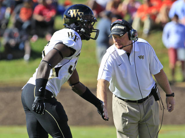 Wake Forest head coach Jim Grobe gives a low-five to Wake Forest defensive end Tylor Harris (36) during the second half of an NCAA college football game against Virginia at Scott Stadium in Charlottesville, Va., Saturday, Oct. 20, 2012. Wake Forest won the game 16-10. (AP Photo/Steve Helber)