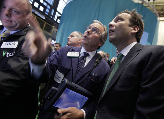Trulia co-founder and CEO Pete Flint , right, talks with trader Thomas Kay, center, as Trulia stock prices for its initial public offering, on the floor of the New York Stock Exchange Thursday, Sept. 20, 2012. Trulia is an online marketplace for homebuyers, sellers, renters and real estate professionals. (AP Photo/Richard Drew)