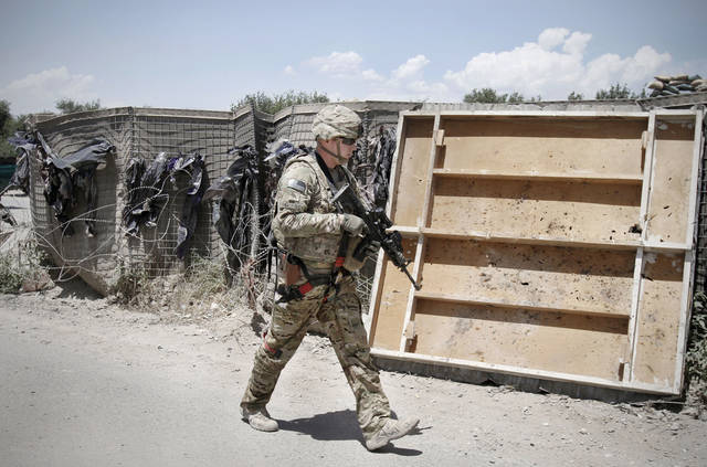 A NATO-led International Security Assistance Force (ISAF) walks toward the police checkpoint in Jalalabad east of Kabul, Afghanistan, Thursday, May 31, 2012. A suicide bomber detonated a vehicle full of explosives outside a district police headquarters in southern Afghanistan on Thursday, killing several policemen, a government official said. (AP Photo/Rahmat Gul)