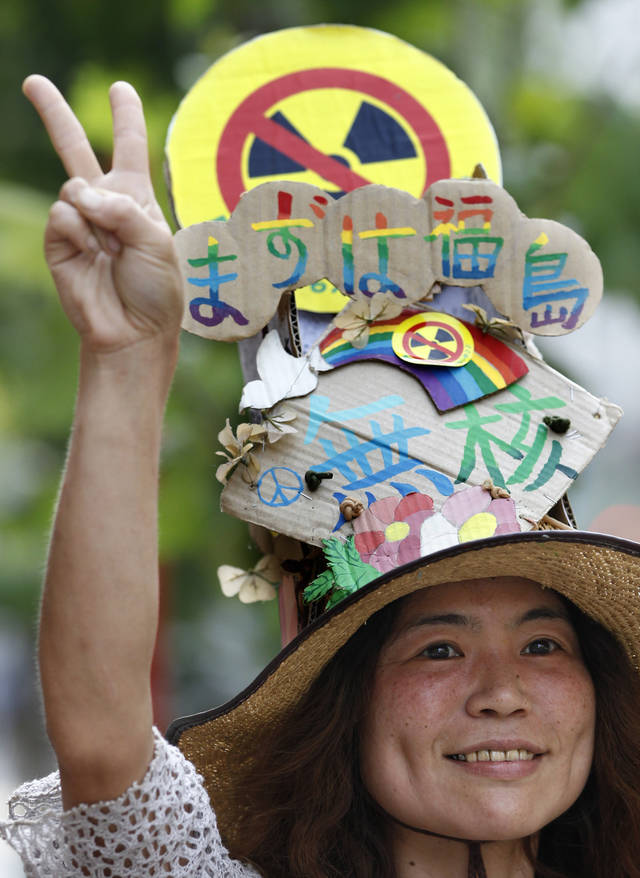 An anti-nuclear protester gestures as the protesters march near the Japan's parliament complex in Tokyo, Sunday, July 29, 2012. Thousands of the protesters rallied to demand the government abandon nuclear power after the accident last year in northern Fukushima. The word on banner reads: No nuclear, Start with Fukushima. (AP Photo/Shizuo Kambayashi)