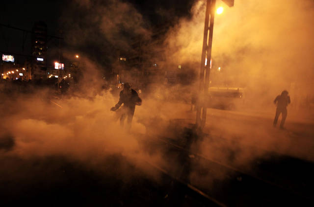 An Egyptian protester throws a tear gas canister back during clashes with riot police in front of the presidential palace in Cairo, Egypt, Friday, Feb. 1, 2013.  Thousands of protesters denouncing Egypt's Islamist president marched on his palace in Cairo on Friday, clashing with security forces firing tear gas and water cannons in the eighth day of the country's wave of political violence.(AP Photo/Khalil Hamra)