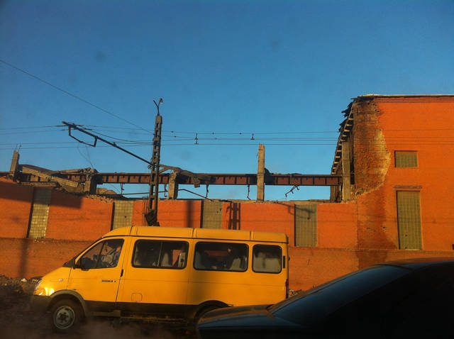 In this photo taken with a mobile phone, a minivan passes a zinc factory building with about 600 square meters (6000 square feet) of a roof collapsed in Chelyabinsk on Friday, Feb. 15, 2013. A meteor streaked across the sky of Russia�s Ural Mountains on Friday morning, causing sharp explosions and reportedly injuring around 100 people, including many hurt by broken glass. (AP Photo/Valentin Kazakov)