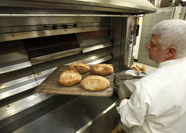 Prairie Thunder Baking Co. owner John McBryde removes loaves of great from a large oven recently at the Prairie Thunder Baking Co. in Oklahoma City. Photo By Paul Hellstern, The Oklahoman <strong>PAUL HELLSTERN - Oklahoman</strong>