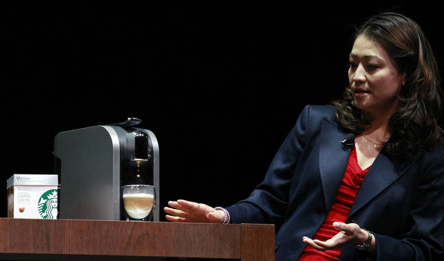 "FILE - Hannah So demonstrates a ""Verismo,"" a single-serving espresso machine, at the annual Starbucks shareholders meeting in this March 21, 2012 file photo taken in Seattle. The Seattle-based company says it will start selling its new single-serve brewer online in mid September 2012 for $199. It plans to start selling the machine in its ubiquitous cafes in October. (AP Photo/Elaine Thompson)"